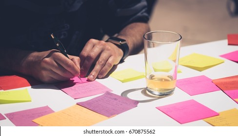 PALO ALTO, CA - JUNE 4: Close up image focusing on hands and pen of a man writing notes for a short story on adhesive notes at a table at Garage Stories VR Hackathon in Silicon Valley on June 4, 2017.