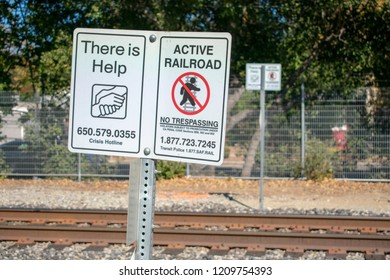 Palo Alto, California, USA - October 19, 2018 - 'There is Help' and 'Active Railroad' signs posted along Caltrain railroad tracks in heavy populated Silicon Valley