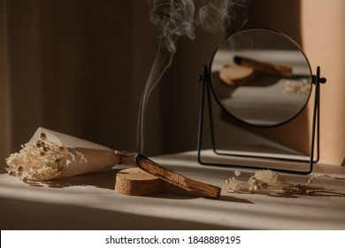 palo santo with jet of smoke, mirror and dried flowers on a neutral background. Abstract trendy picture. Minimalistic wabi sabi style.