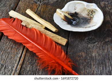 Palo Santo smudge sticks with a bright orange feather.