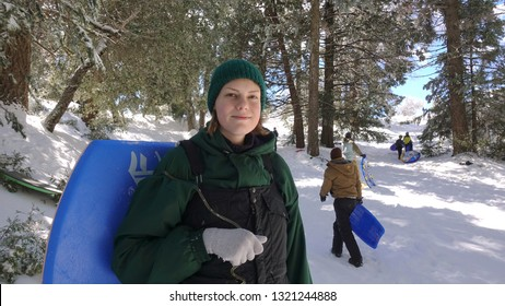 Palomar Mountain, CA / USA - February 22, 2019: A California teen girl having fun in the snow, people sledding with boogie boards