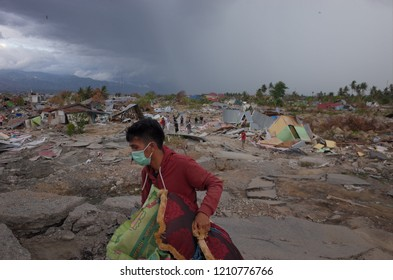 PALU, INDONESIA - OCTOBER 11th, 2018: Victims of the earthquake and tsunami in the National Housing Agency of Balaroa scavenge the remains of their ruins on October 11th, 2018 in Palu, Indonesia. A ts