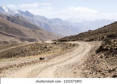 Pamir Highway in the desert landscape of the Pamir Mountains in Tajikistan. Afghanistan is on the left