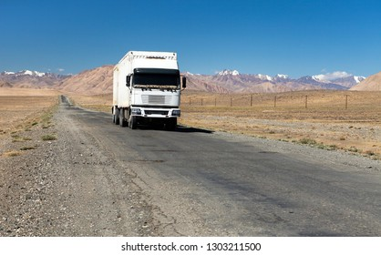Pamir highway or pamirskij trakt and white truck. Landscape around Pamir highway M41 international road, Pamir mountains in Tajikistan