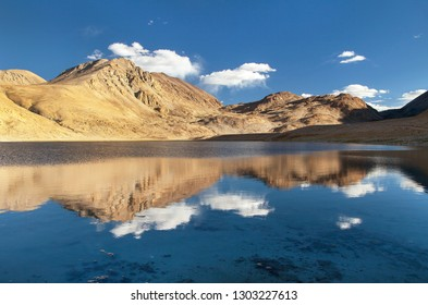 Pamir mountains near Pamir highway, evening view of small lake and mounts mirroring in lake, Tajikistan
