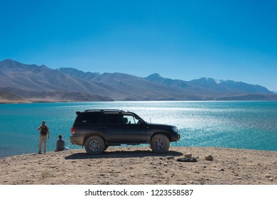 Pamir Mountains, Tajikistan - Aug 21 2018: Toyota Land Cruiser are stoped on the Yashilkul Lake in Gorno-Badakhshan, Tajikistan.