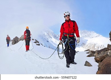 Pamiro-Alay, Kyrgyzstan - May 02, 2013: Group of mountaineers ascent to the mountain using the rope on a complex slope is composed of rock and snow