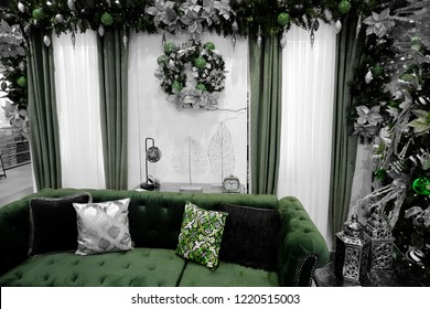 PAMPANGA, PHILIPINES - 24 OCTOBER 2018: Sofa and pillows in green isolated on black and white background with christmas decorations