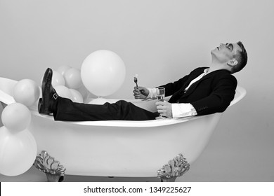 Pampering himself in bath. Mime actor enjoy bathing in bath tub. Mime man has celebration party with food and drink. Comedian actor celebrate holidays. Happy bubble bath day. Bathing and relaxing.