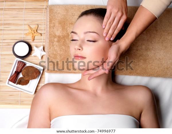 Verwöhnen und Massagen für das schöne Gesicht der jungen Frau im Spa-Salon - Innenbereich