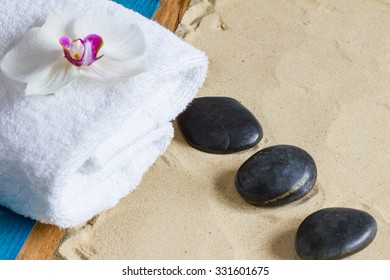 Pampering therapy at the beach with hot stone massage. Black basalt stones, white towel, orchid flower, aqua painted wood on a sand background.  Closeup, copyspace, selective focus