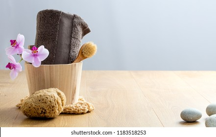 Pampering Turkish bath and sensuality. Natural sponge and wooden face dry brush for detox and wellness over pure orchids and zen pebbles, copy space