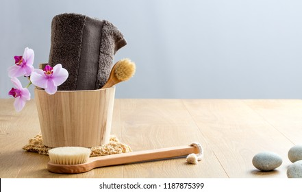 Pampering Turkish bath and sensuality. Wooden body and face brushes for detox dry brushing over pure orchids and spa pebbles, copy space