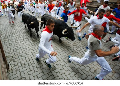 PAMPLONA, SPAIN - JULY 10, 2017: Bulls and people running on the street during the festival of San Fermin. Bulls of the cattle ranch of Fuente Ymbro in the fourth run of the festival
