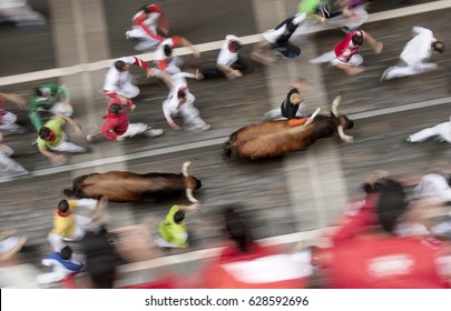 PAMPLONA, SPAIN - JULY 12, 2014: Bulls and people are running in street during San Fermin festival