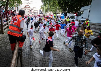 PAMPLONA, SPAIN - JULY 12, 2018: Bulls and people running on the street, encierro, during the festival of San Fermin. Bulls of the cattle ranch of Victoriano Del Rio