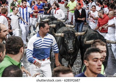 PAMPLONA, SPAIN - JULY 14, 2014: Bulls and people are running in street during San Fermin festival
