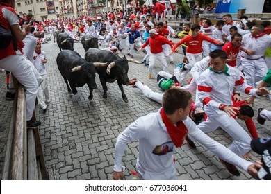 PAMPLONA, SPAIN - JULY 14, 2017: Bulls and people running on the street in the festival of San Fermin. Bulls of Eduardo Miura in the eighth and last running of the bulls of the festival of San Fermin