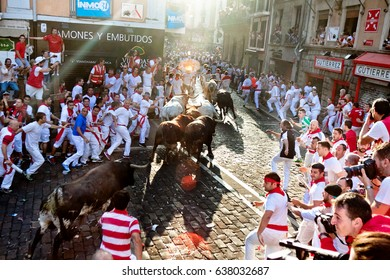PAMPLONA, SPAIN - JULY 7, 2015: Bulls and people are running in street during San Fermin festival. Festival has been held annually for several centuries