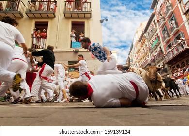 PAMPLONA, SPAIN-JULY 12: People run from bulls on street during San Fermin festival in Pamplona, Spain on July 12, 2013..