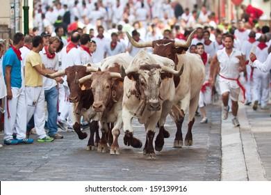 PAMPLONA, SPAIN-JULY 9: People run from bulls on street during San Fermin festival in Pamplona, Spain on July 9, 2013..