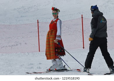 Pamporovo, Bulgaria - March 03, 2018: Skiing with Bulgarian flags at Pamporovo ski resort, Bulgaria. People dressed with traditional Bulgarian clothes skiing with the Bulgarian national flag.