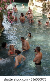 PAMUKKALE, TURKEY - MAY 27, 2014 - Russians and other tourists swim in the thermal pools amidst ancient Roman columns of the spa at Pamukkale Turkey