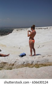 PAMUKKALE, TURKEY - MAY 27, 2014 - Young woman in  bikini wth dragon tattoo  sunbathing on the travetine terraces  at Pamukkale,  Turkey