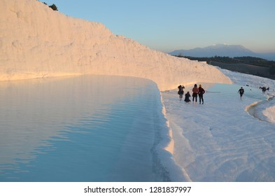 Pamukkale/turkey_18 Dec 2018: The calcium travertines at Pamukkale (Hierapolis), Turkey, near Denizli. Tourists walking in the hot spring water travertine during sunset time.