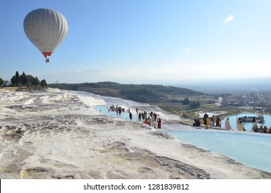 Pamukkale/turkey_18 Dec 2018: The calcium travertines at Pamukkale (Hierapolis), Turkey, near Denizli. Tourists walking in the hot spring water travertine during afternoon time.