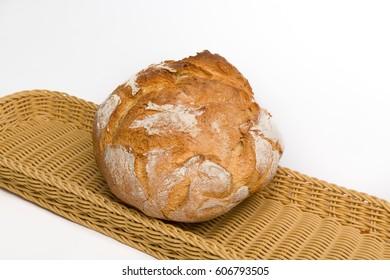 Pan de payés redondo sobre cesta de mimbre y fondo blanco