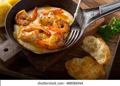 A pan of delicious fresh homemade cajun style shrimp and grits with cheddar biscuit.