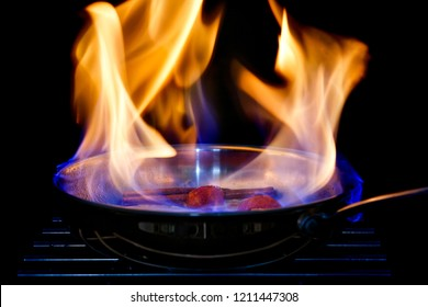 A pan with flames flambeing fruit. Black background.