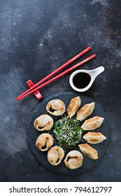 Pan fried asian dumplings with seaweed salad and soy sauce, flat-lay on a dark weathered metal background with copyspace