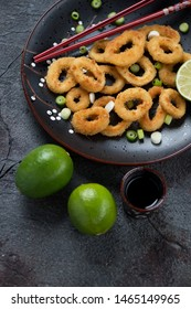 Pan fried calamari rings in panko breading, high angle view on a dark grey stone surface, studio shot