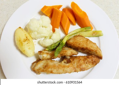 Pan fried chicken breast, coated with seasoned flour and served with asparagus and steamed vegetables