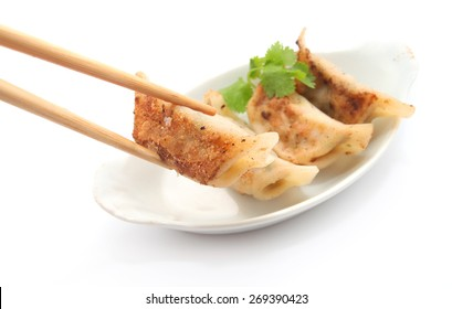 Pan Fried Dumpling pick up by chopstick isolated on white