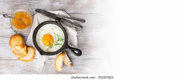 Pan of fried egg, crispy baguette and fruit jam on white rustic wooden table, top view. Breakfast time concept, long web format