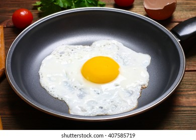 Pan of fried eggs, with cherry-tomatoes and parsley on a wooden table surface