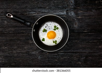 pan with fried eggs on a wooden background