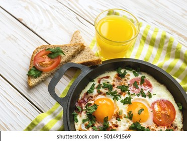 Pan of fried eggs, tomatoes and parsley with bread  and orange juice on white wooden table. Breakfast