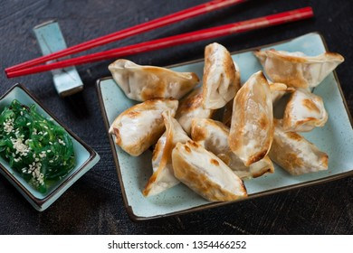 Pan fried gyoza dumplings with seaweed salad, high angle view on a dark brown stone background