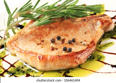 Pan fried pork chop decorated with rosemary and balsamico