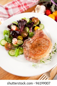 Pan Fried Pork Chops Served with Greens and Tomato Salad