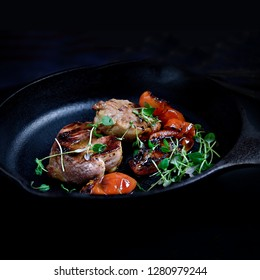 Pan fried pork medallions with roasted cherry tomatoes with thyme herb garnish in an iron skillet, ready for serving. Copy space. The perfect image for your bistro or restaurant menu cover art.