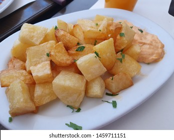Pan Fried Potatoes and Spicy Sauce on a White Plate, Delicious Restaurant Tasty Dish with Herbs, Orange Juice on Background, Crispy French Fries