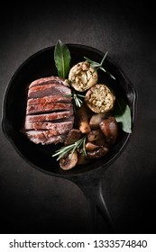Pan fried in a wrought iron skillet roasted wild boar fillet with garlic mushrooms and sage, apple and onion stuffing balls with bay leaves and rosemary herb garnish.