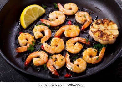 pan of grilled shrimps on a dark table