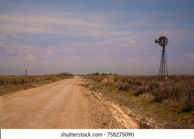 Pan Handle, Oklahoma - 4/11/2010: A gravel county road and a working windmill in the Oklahoma panhandle, about 50 miles west of Woodward.