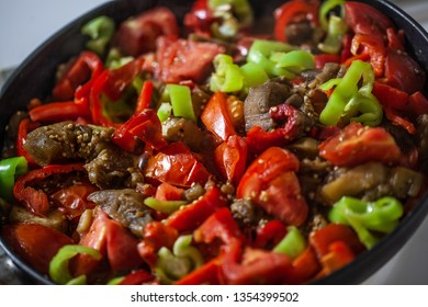 A pan with meat ragout with red and green pepper and tomatoes